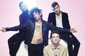 The 1975 band members in front of a pink background