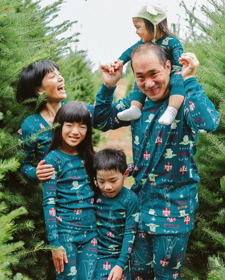 a family in matching green star wars pajamas with images of baby yoda and the mandalorian on them