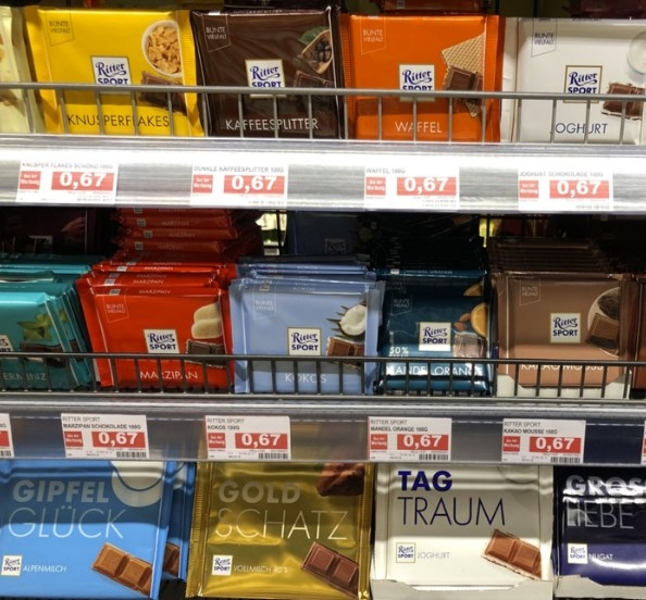 Grocery store shelf stocked with various German Ritter chocolate bar flavors