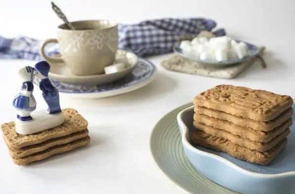 White table organized with a cup of coffee and tray of sugar cubes, as well as a tray of neatly stacked plain cookies