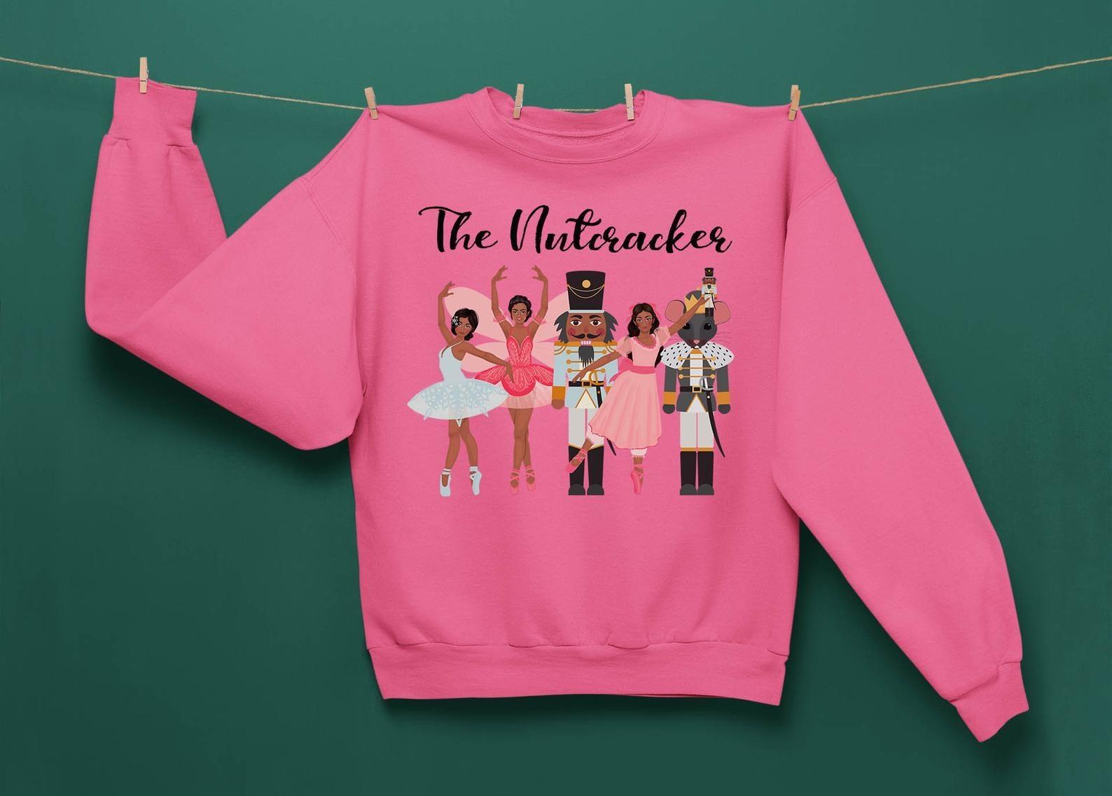 a pink sweatshirt with the nutcracker characters on it in dark skintones