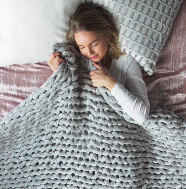 model cuddles with large knit blanket