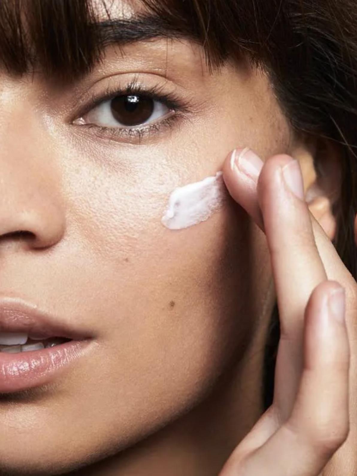 A model applying the moisturizer to their cheekbone