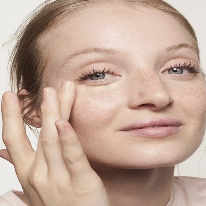 A model applying the concealer to their undereye