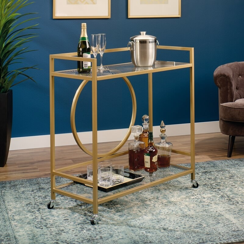 Gold bar cart on wheels with glasses and alcohol on the shelves