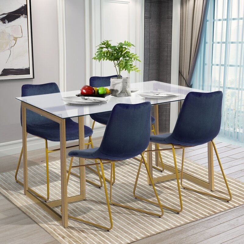 Glass top dining table with gold legs and four blue velvet chairs