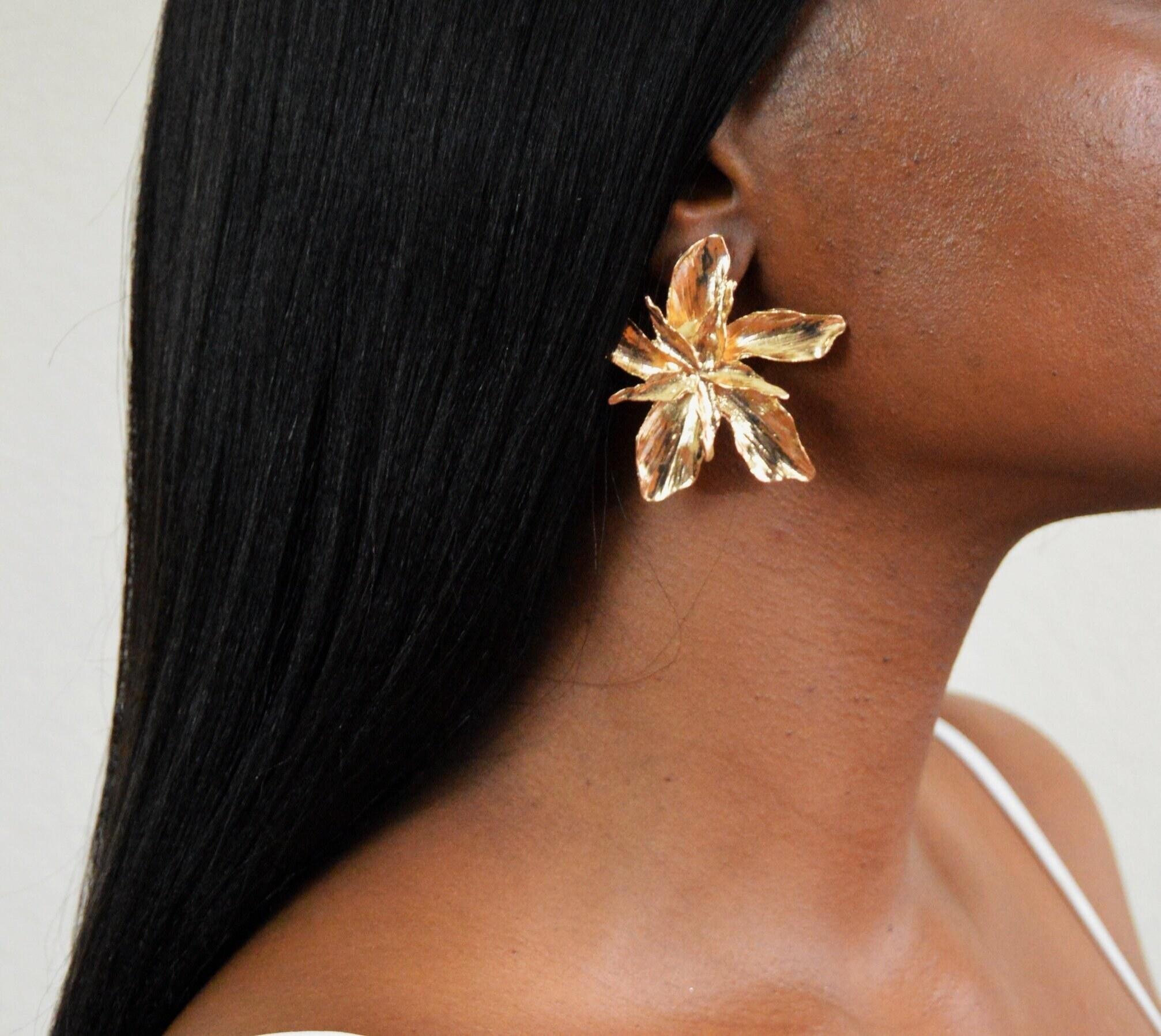 The large gold flower earring on a model's ear