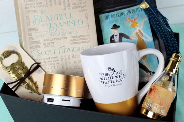 box with a copy of the beautiful and damned plus a feather bottle opener, champagne jelly beans, a mug, and some coffee