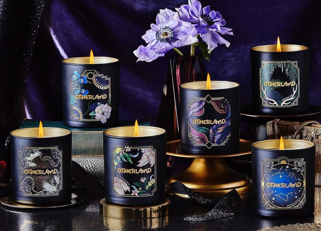 six black candles with wintery illustrated labels