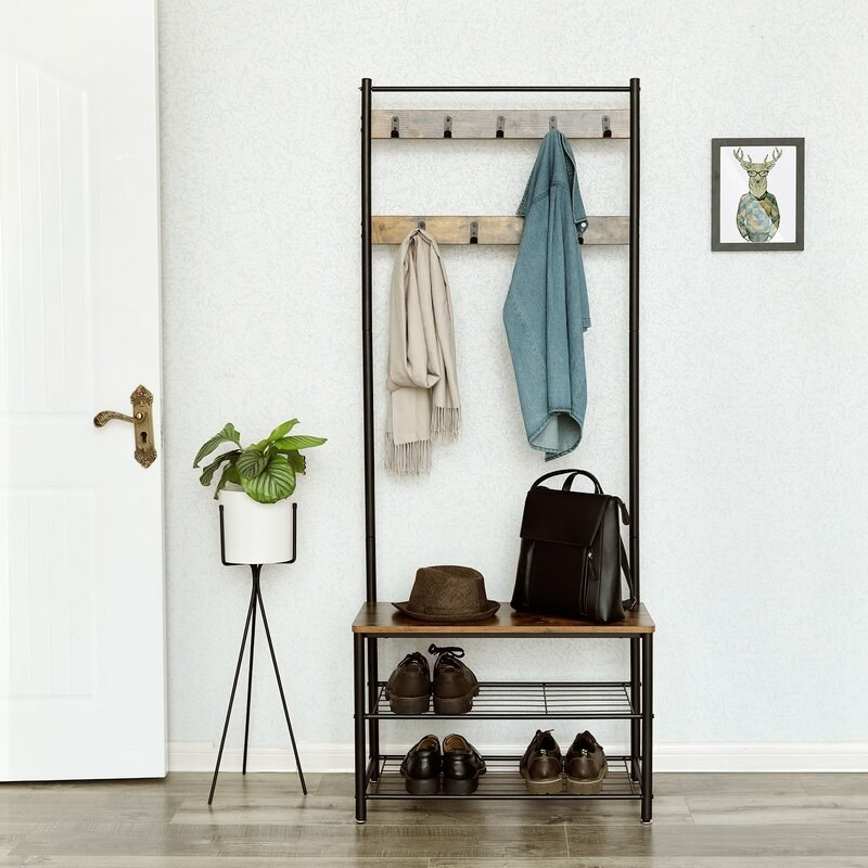 Wood frame hall tree with a shirt on the hooks at the top and accessories and shoes on the bottom shelves