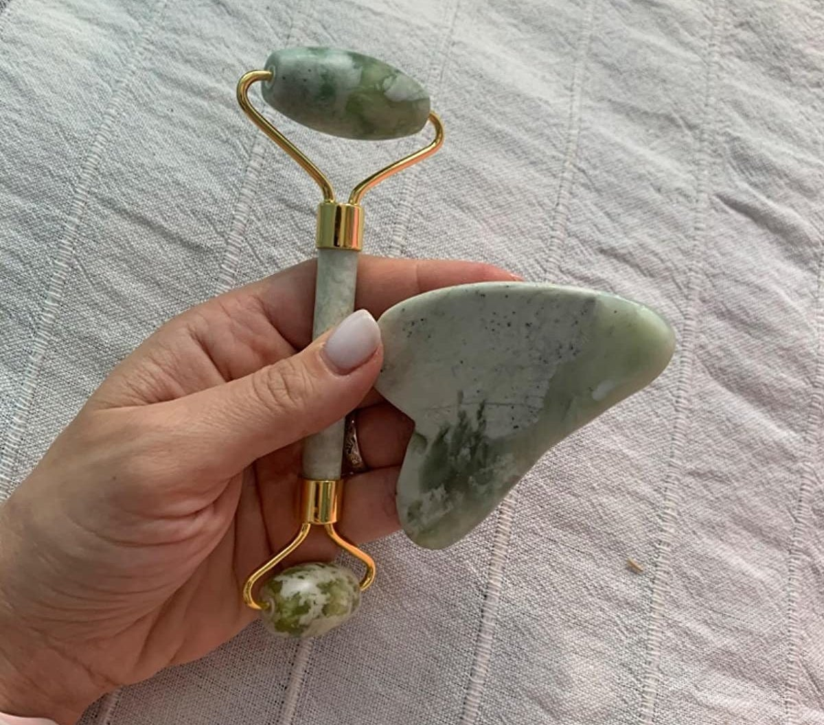 A reviewer holding the green double-sided roller and gua sha
