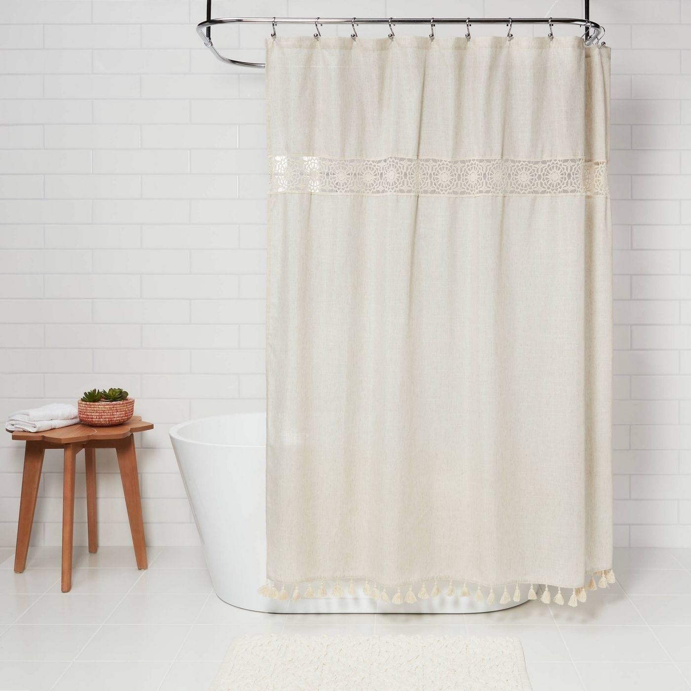 The shower curtain, which is cream-colored and has a linen look, with small fabric tassels on the bottom and crochet details near the top