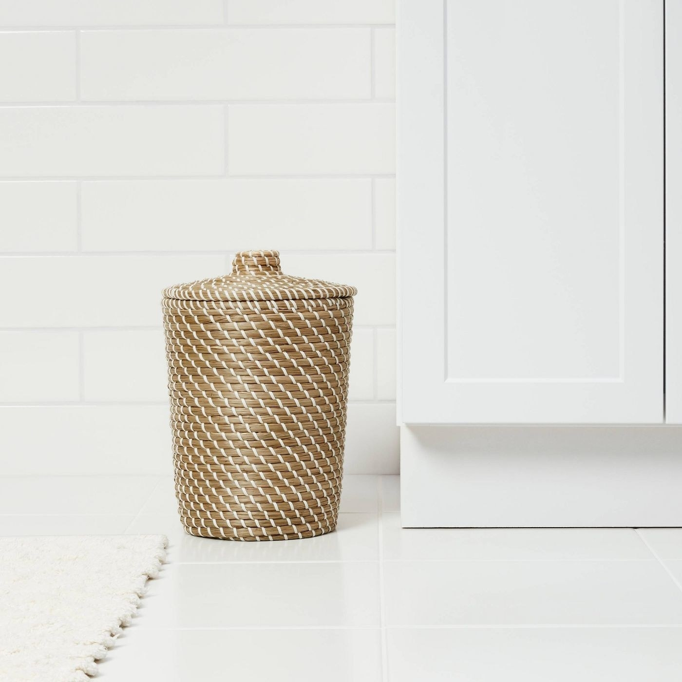 The woven wastebasket, which is made from strands of light brown and white fiber, and has a top with a small handle