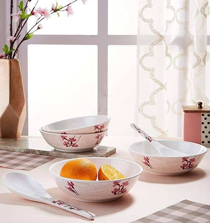 White ceramic bowls and spoons with floral designs.