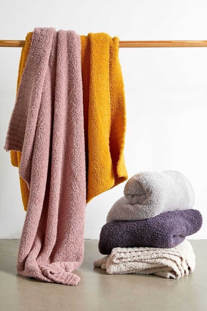 the blankets in pink, yellow, purple, gray, and cream