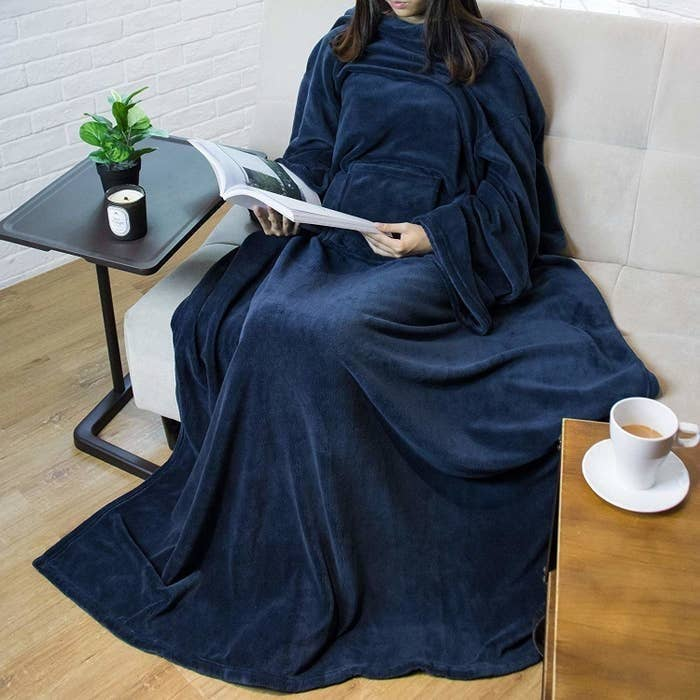 A woman covered in a navy blue fleece blanket, with her hands jutting out of the sleeves.