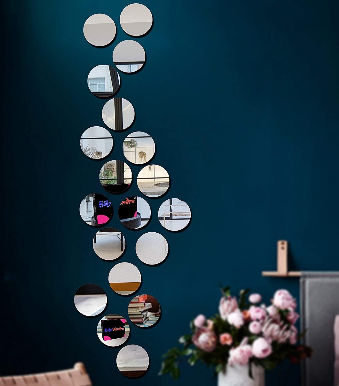 Circular mirror stickers on blue wall.