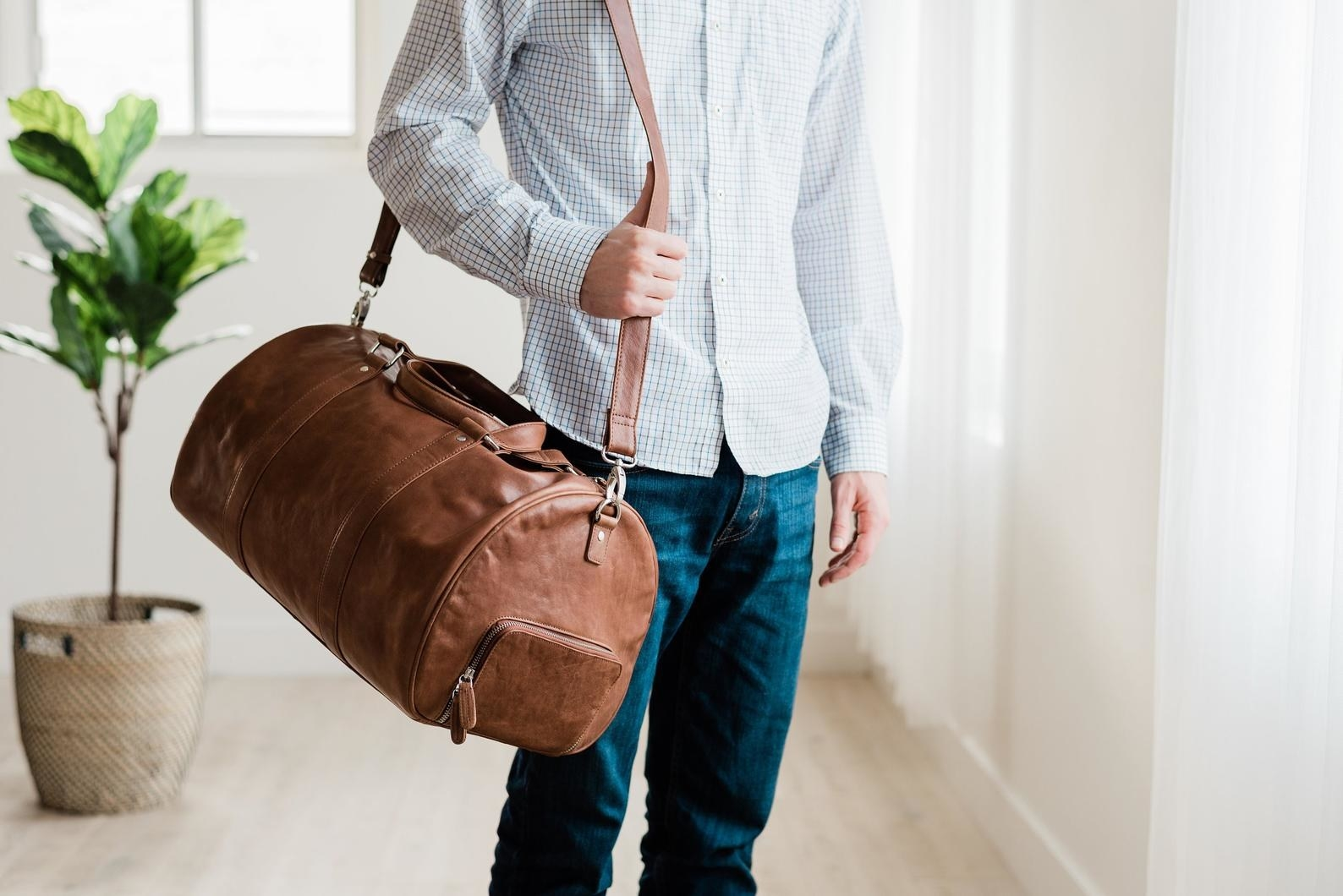 The oval-shaped brown leather bag with a long shoulder strap over a model's shoulder