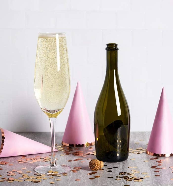 A bottle of prosecco beside a glass holding the entire bottle