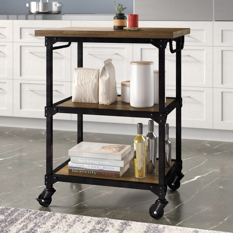 a kitchen cart with wooden shelves and a black frame on wheels in a kitchen