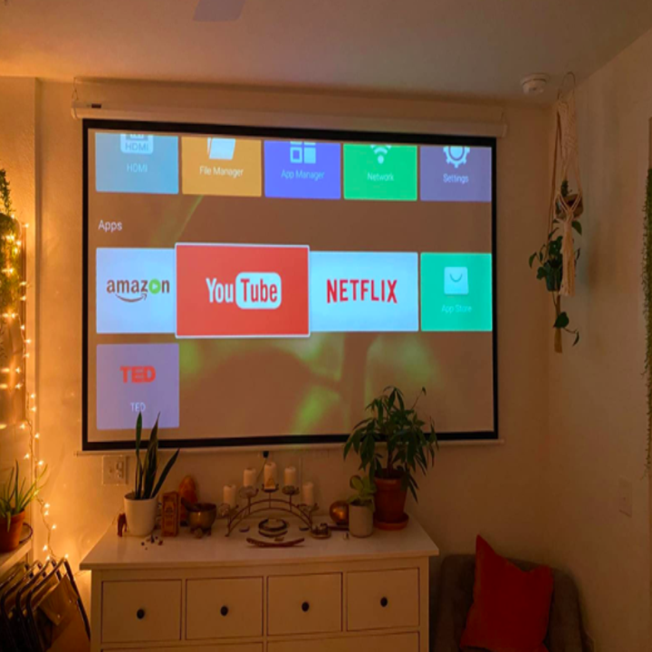 reviewer photo showing the projector displaying its home page on a large screen in the reviewer's living room