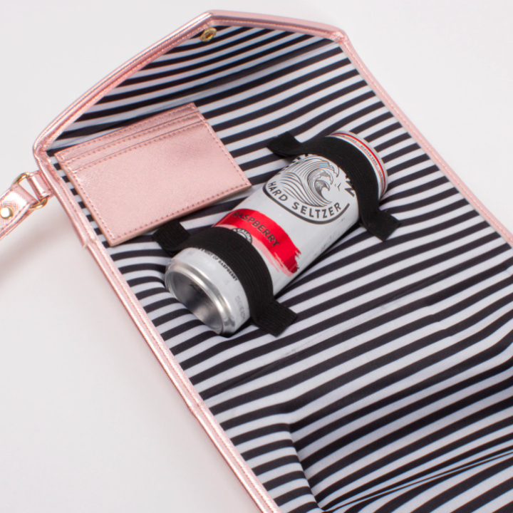 The clutch open revealing a can of White Claw.