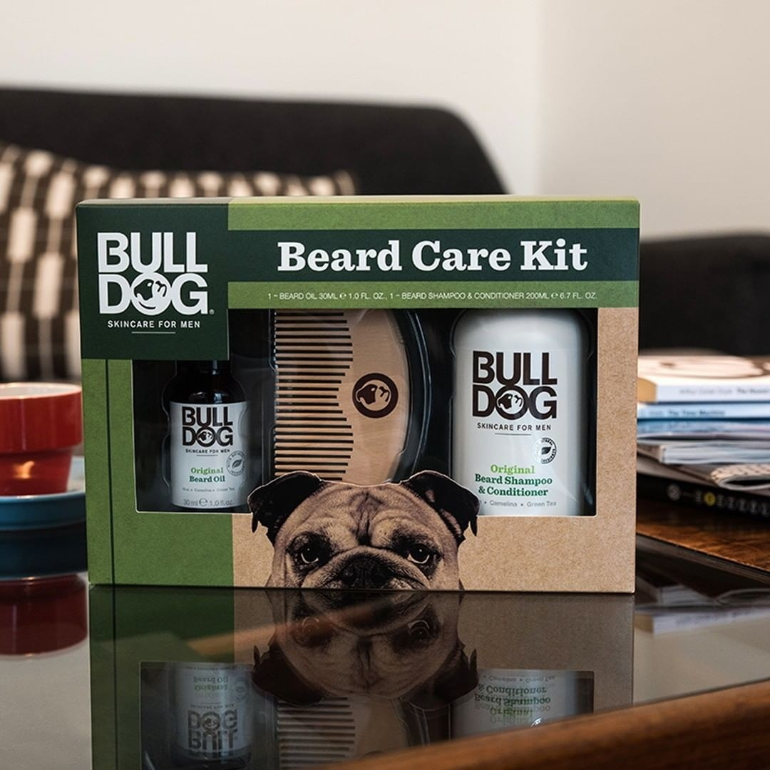 The boxed set of beard oil, shampoo, and comb on a coffee table next to a stack of magazines