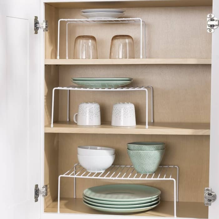 three white wire racks with plates on them on three different shelves