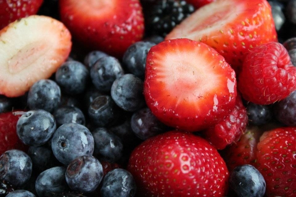 Close-up of mix of cut strawberries and whole blueberries