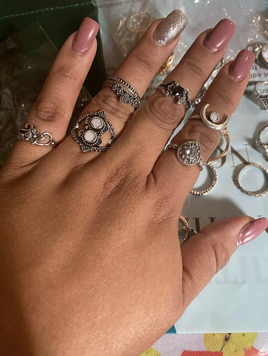 A reviewer's hand with the rings on their fingers and above their knuckles in silver vintage designs