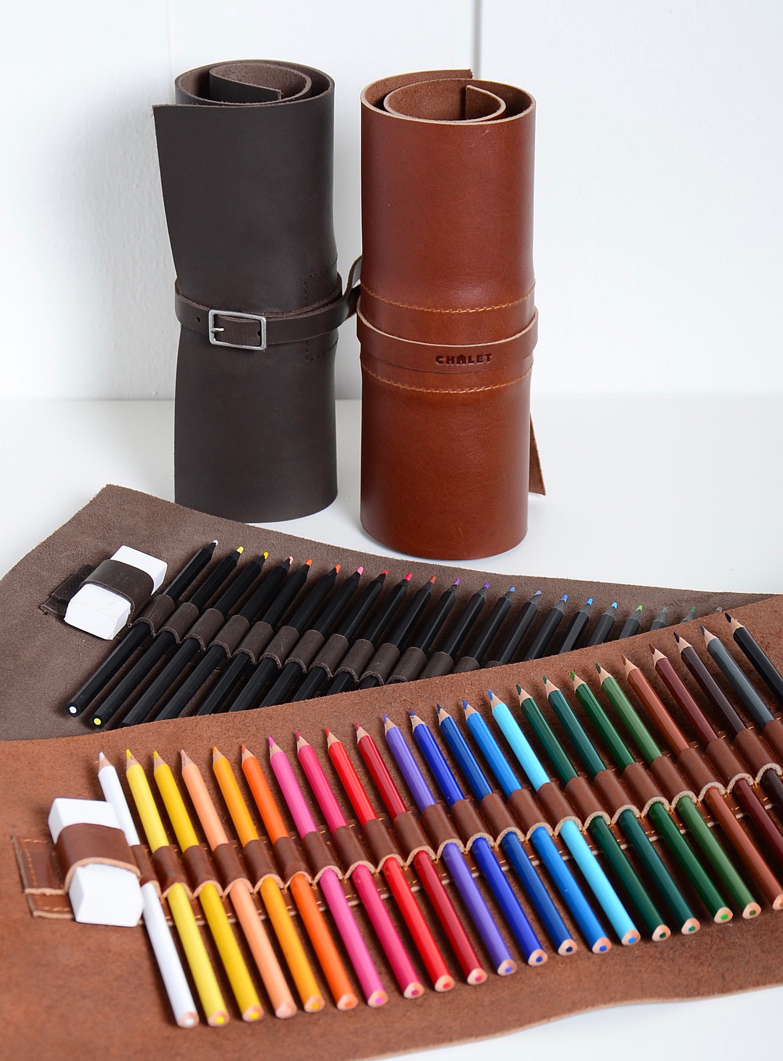 A leather art supply kit filled with coloured pencils and an eraser