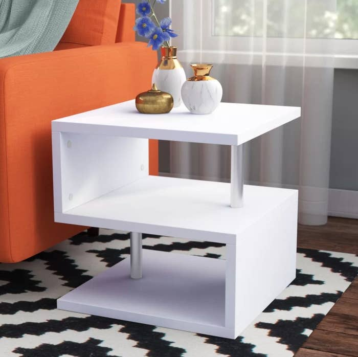 An end table with storage in white and metal