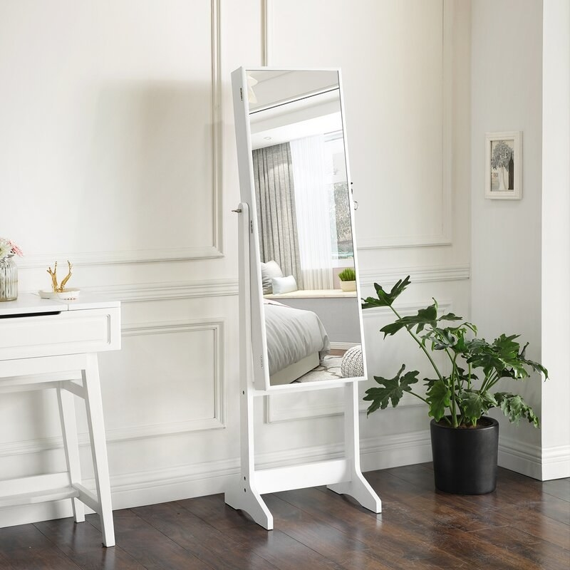 a white body mirror that opens up to a jewelry chest in a bedroom