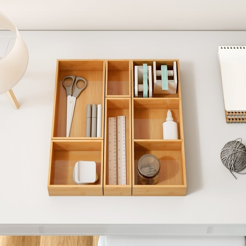 an arragnement of bamboo trays holding office supplies