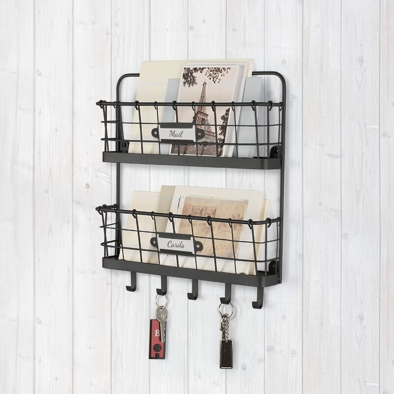 a black wire two tiered letter holder with key hooks hanging on a wall