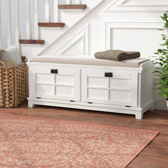 a white storage bench with a tan cushion on top in a hallway