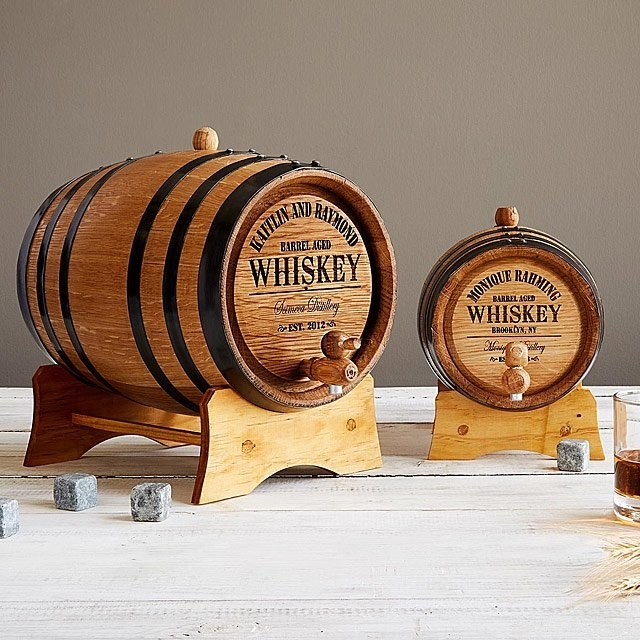 A small and large barrel on stands with spouts and personalized label on the front