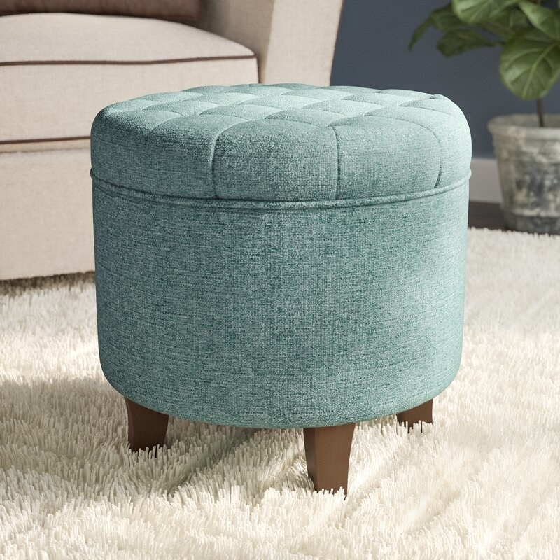 a turquoise tufted storage ottoman with brown legs on a white rug