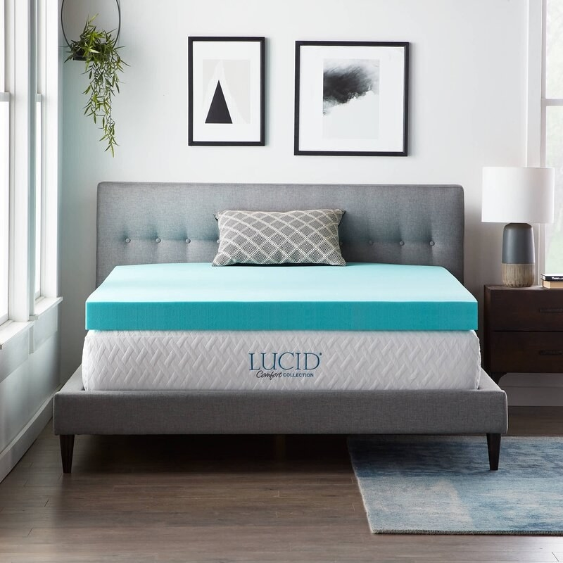 a turquoise mattress topper on top of a mattress on a bed in a bedroom