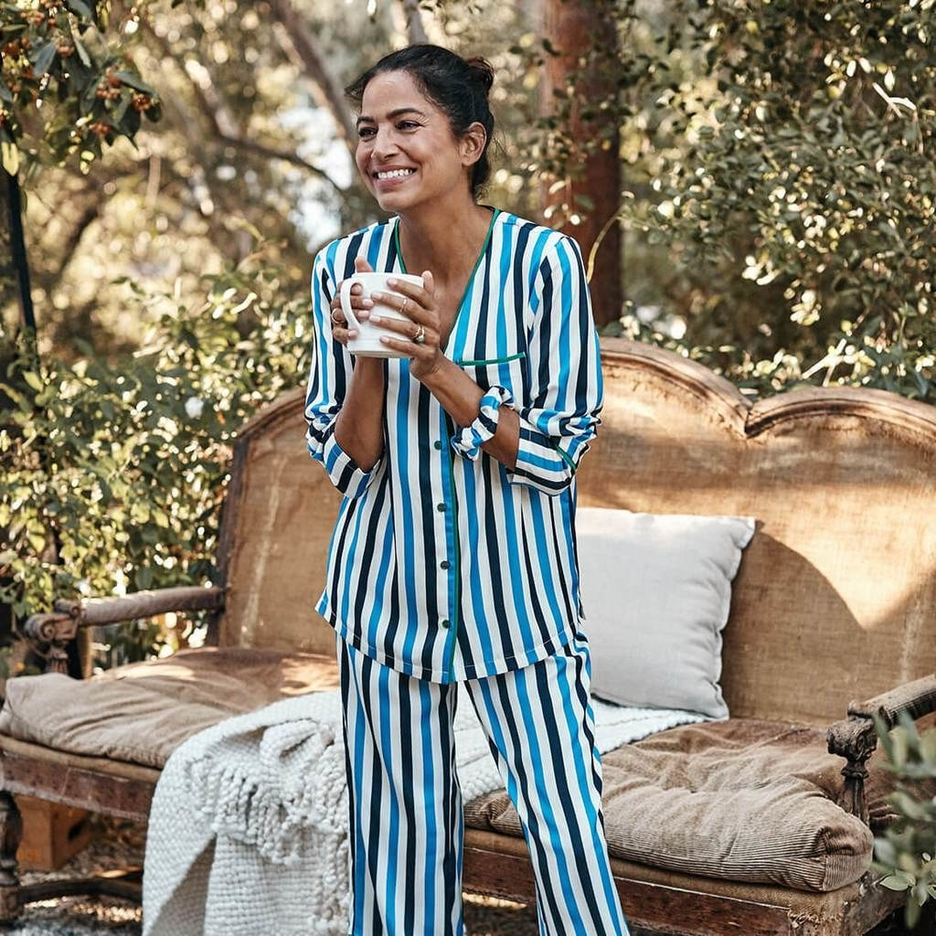 a model outdoors holding a mug in long sleeve and pants pajamas with vertical blue and black stripes