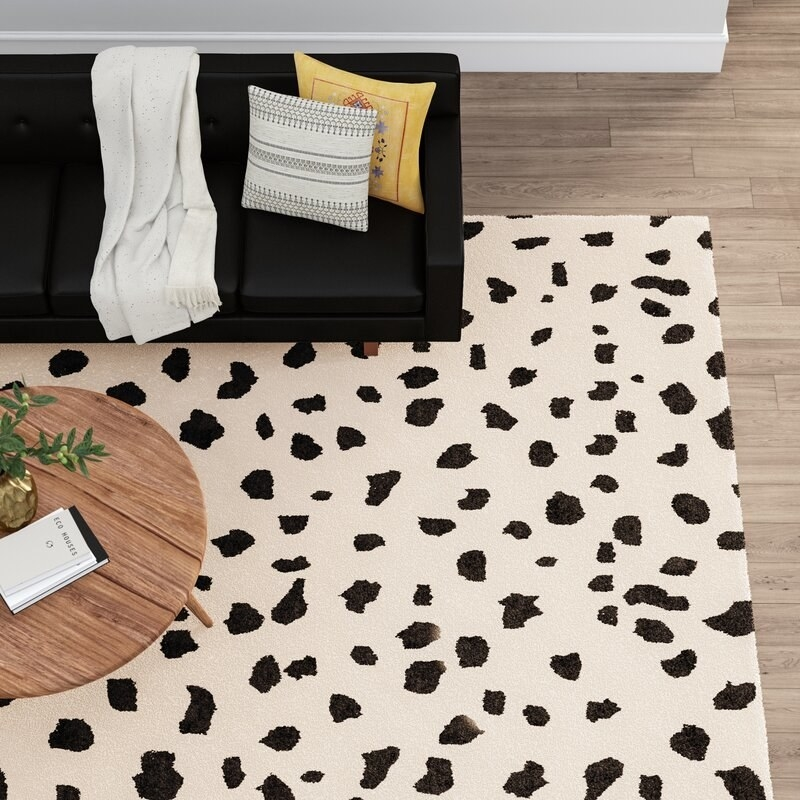 an animal print wool rug with a beige base and black spots in a living room