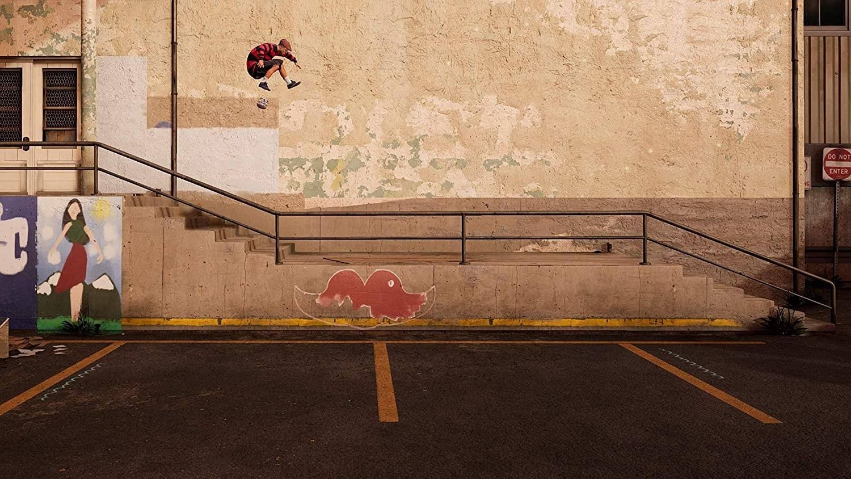 A skater doing a kick flip down a flight of concrete steps