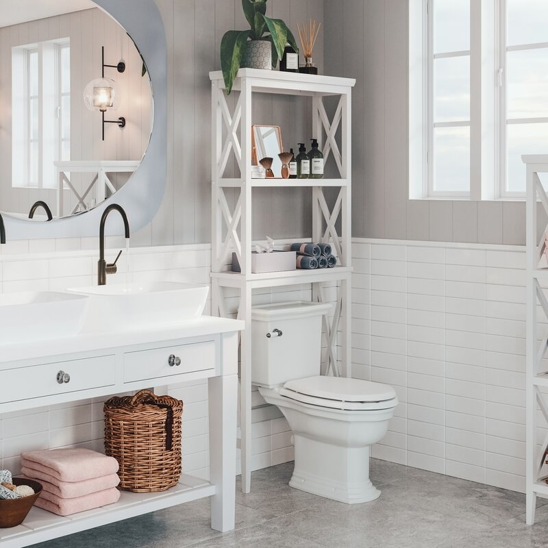 a white wooden over the toilet storage system that has two shelves in a bathroom