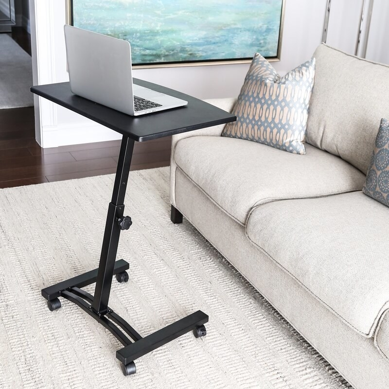 a black laptop cart on wheels in a living room holding a laptop
