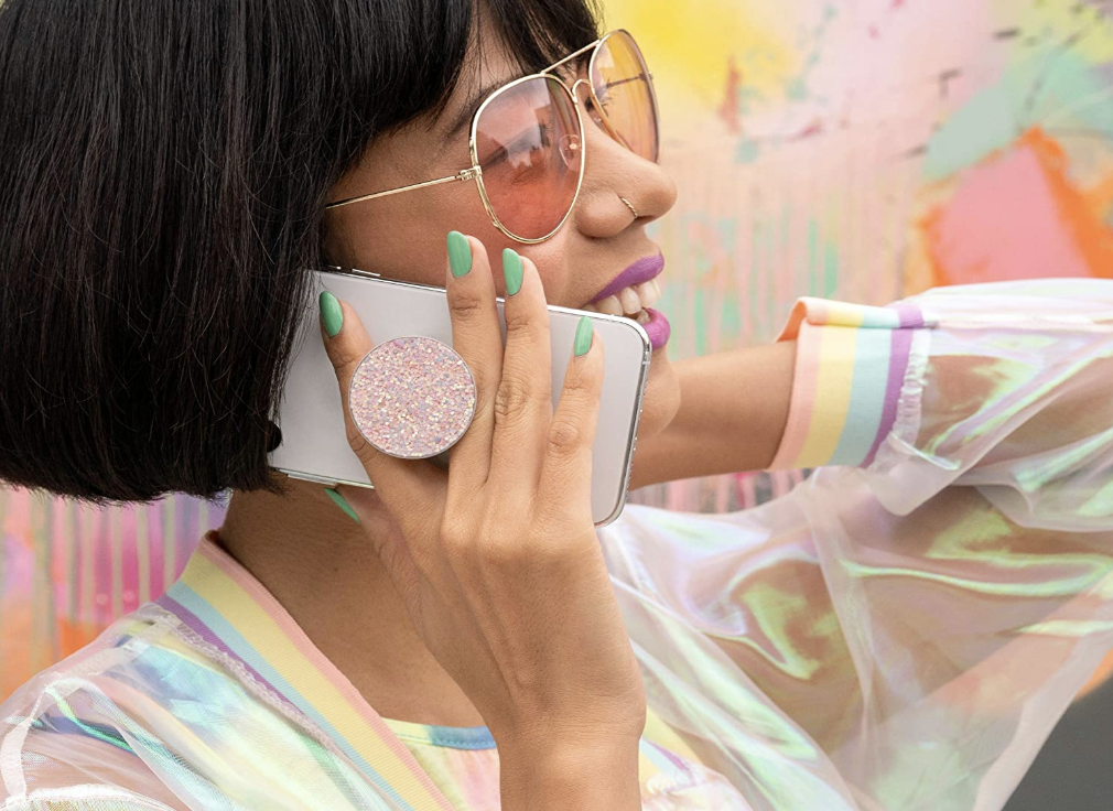 A model talking on their phone with their fingers around the sparkly pop up attachment on the back of their phone
