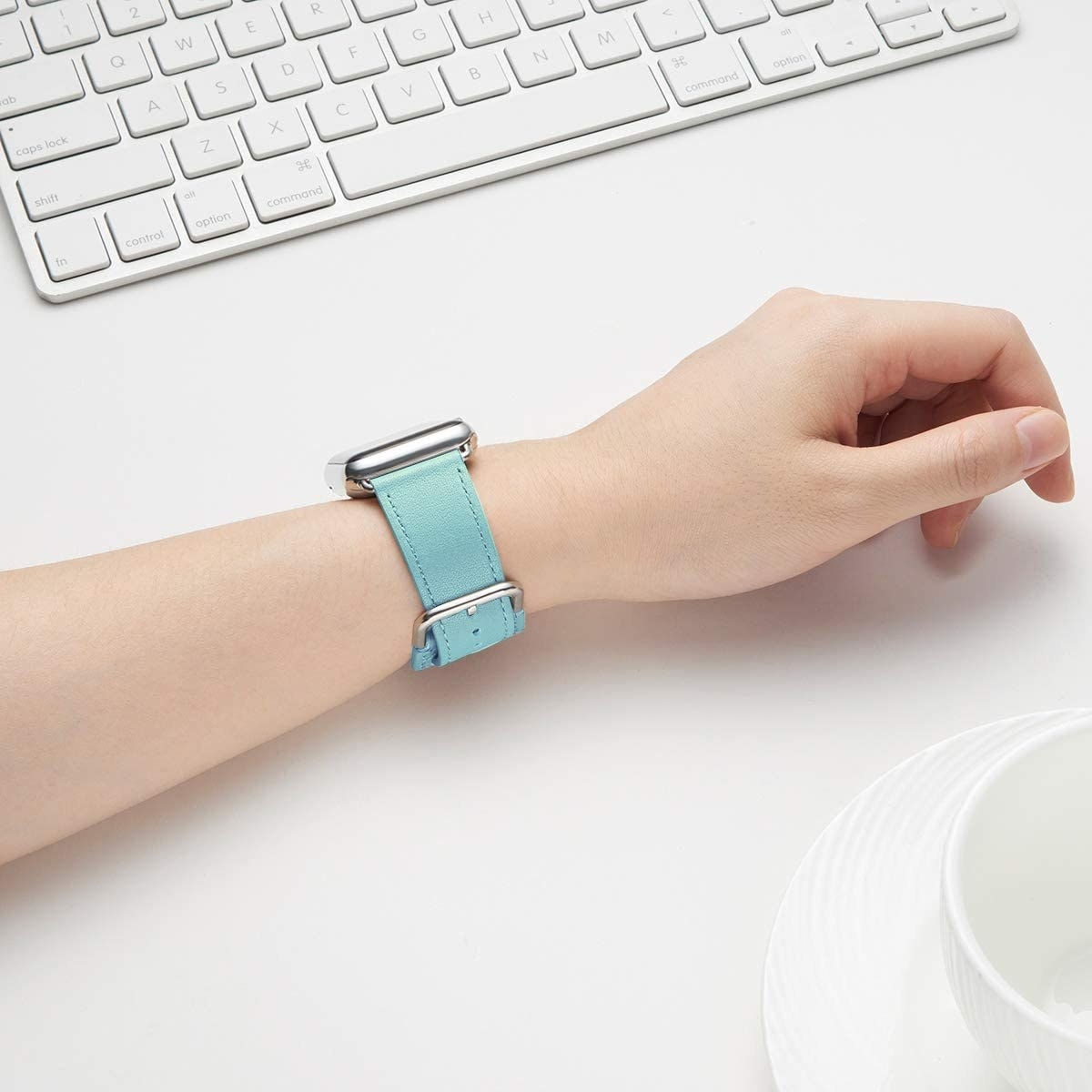 Model with a light blue Apple watch band around their wrist
