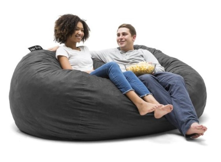 Two models on big gray bean bag chair