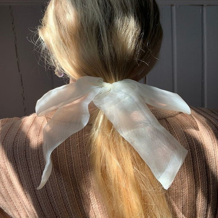 model wearing a white sheer bow scrunchie in her hair