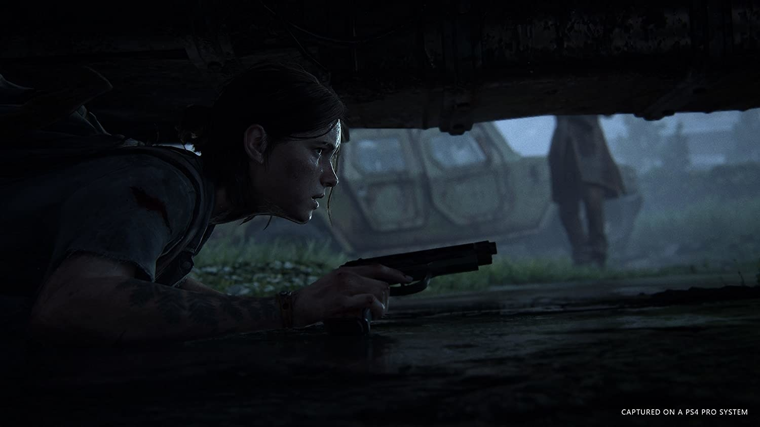 A character crouched under a vehicle aiming a gun