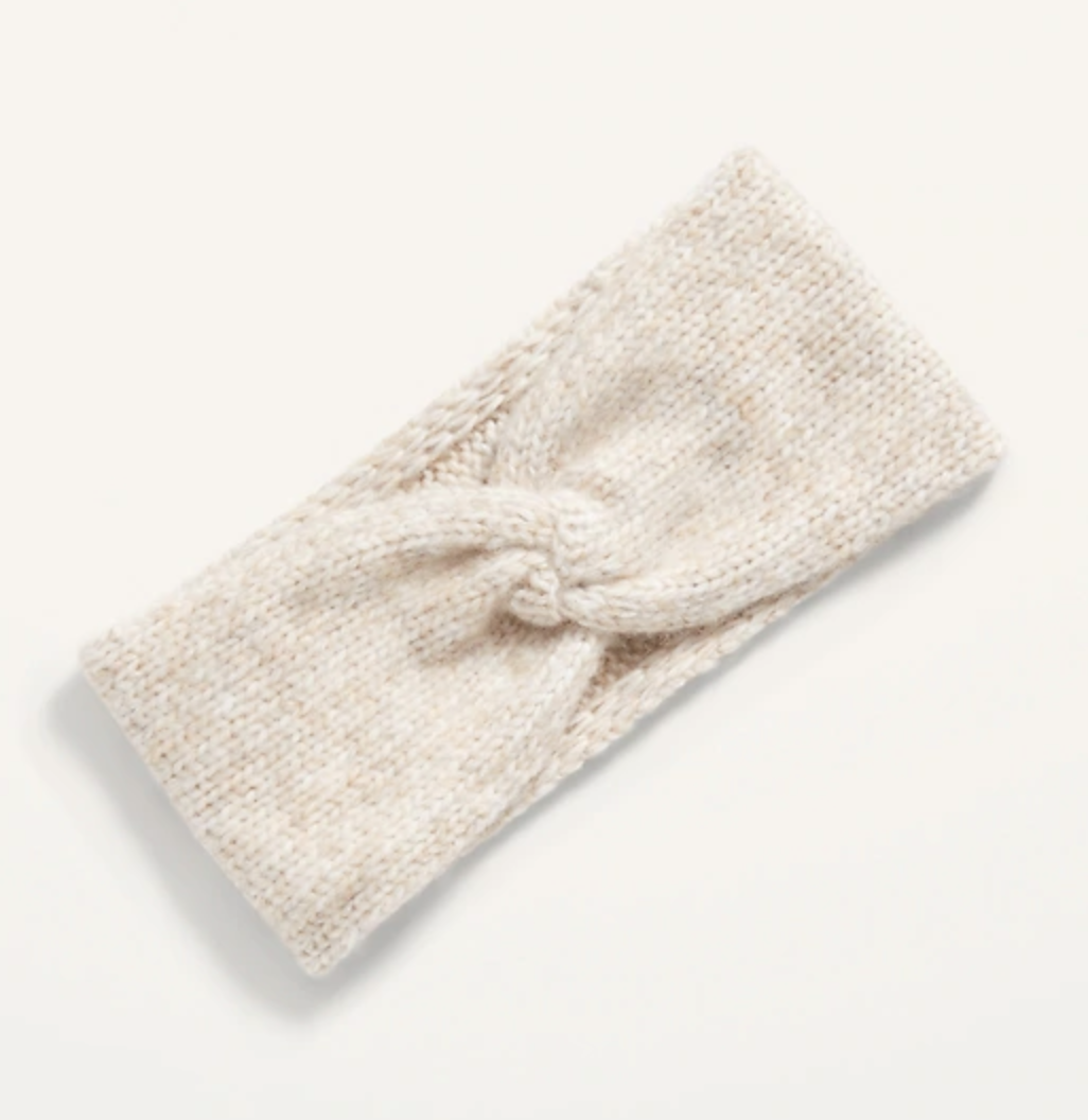 An ivory colored knit headband ear warmer with a twist front